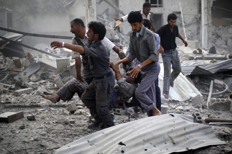Syrian emergency personnel carry a wounded man following air strikes