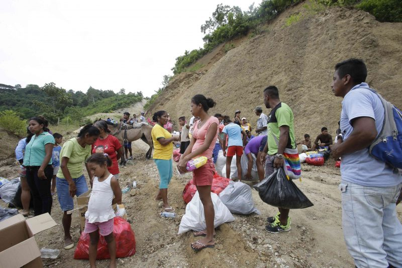 Victims of the 7.8-magnitude earthquake that hit Ecuador's Pacific coast, carry emergency supplies that they received from an army truck in Cholote, Ecuador, Thursday, April 21, 2016. President Rafael Correa said Ecuador's worst earthquake in decades caused billions of dollars of damage and he is raising sales taxes and putting a one-time levy on millionaires to help pay for reconstruction. (AP Photo/Dolores Ochoa)