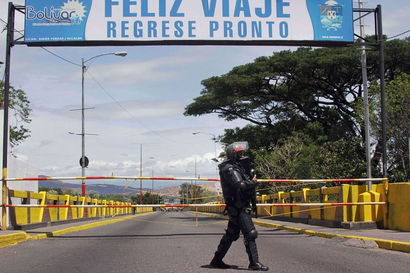 Venezuelan troops in riot gear stand by the Venezuela-Colombia border in San Antonio, Venezuela, on August 20, 2014. Venezuela's President Nicolas Maduro has ordered part of frontier with Colombia closed after four people were wounded in an overnight attack along the border. AFP PHOTO/GEORGE CASTELLANO