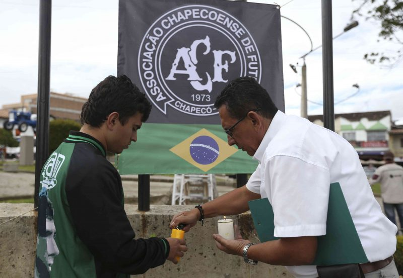 Fans of Colombia's Atletico Nacional light candles in front the Chapecoense soccer team logo in La Union, Colombia, Tuesday, Nov. 29, 2016. A chartered plane that was carrying the Brazilian soccer team Chapecoense to the biggest match of its history crashed into a Colombian hillside and broke into pieces, killing most of the passengers, Colombian officials said. (AP Photo/Fernando Vergara)