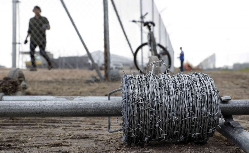 Workers install barbed-wire on top of a fence at a U.S. Customs and Border Protection  temporary holding facility near the Donna-Rio Bravo International Bridge, Wednesday, Dec. 7, 2016, in Donna, Texas. The tent facility will primarily be used as a temporary holding site for children and families who have entered the county illegally. (AP Photo/Eric Gay)