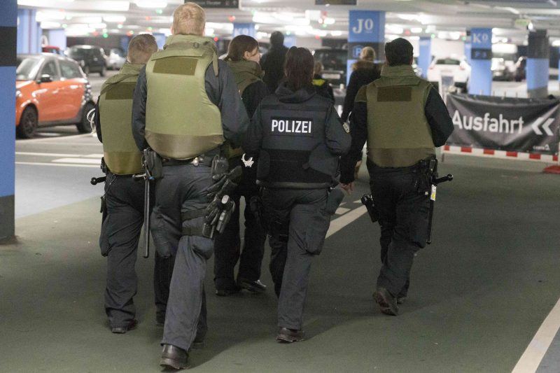 """In this Dec. 22, 2016 photo police units walk through the parking lot of the shopping centre """"Centro"""" in Oberhausen, Germany. Two men have been arrested in Duisburg on the suspicion of planning a terror attack on the shopping centre. (Arnulf Stoffel/dpa via AP)"""